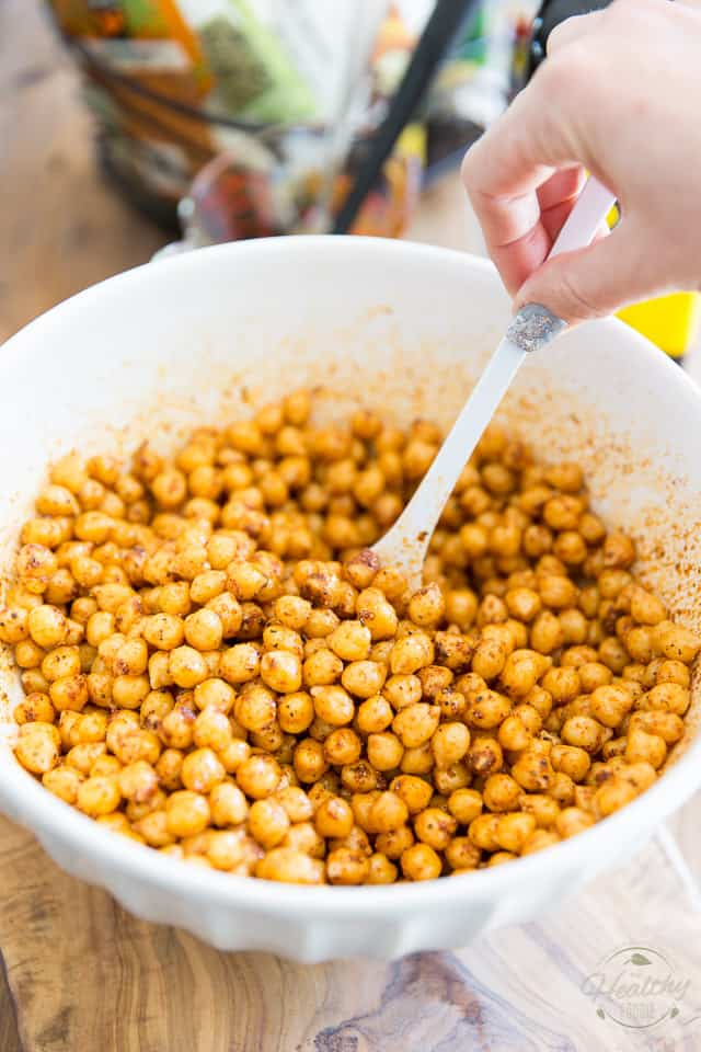 Cooked chickpeas and tex mex seasoning in a white bowl getting tossed with a large plastic spoon