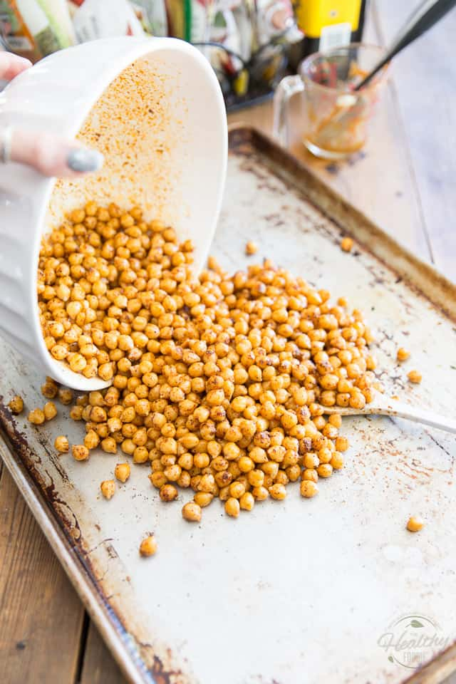 Seasoned chickpeas are getting transferred to a large baking sheet