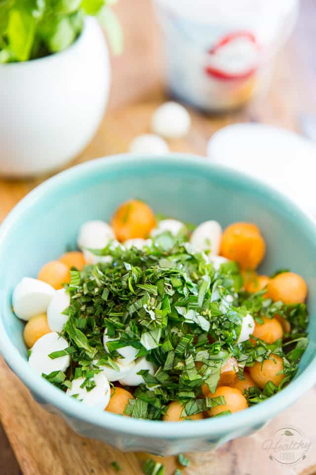 Melon balls, mini bocconcini and fresh herbs in a blue ceramic bowl