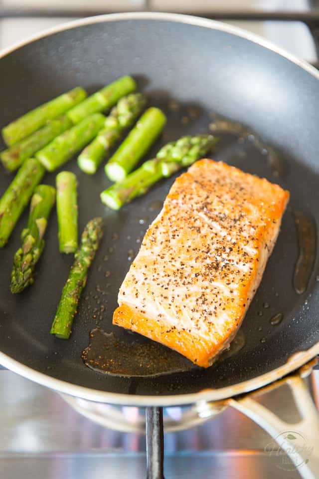 A salmon fillet and some chunks of asparagus cooking in a non-stick pan