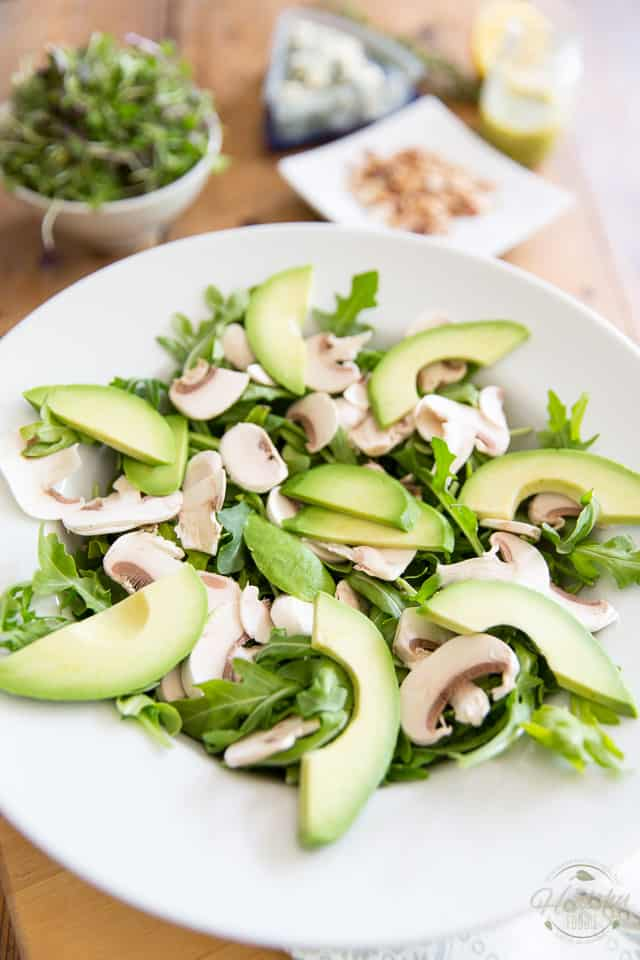 Arugula, sliced mushrooms and avocados arranged in a white ceramic bowl