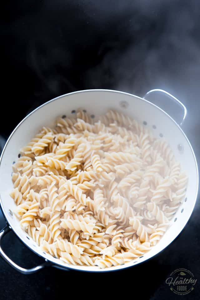 Overhead view of cooked whole wheat rotini pasta in a white colander