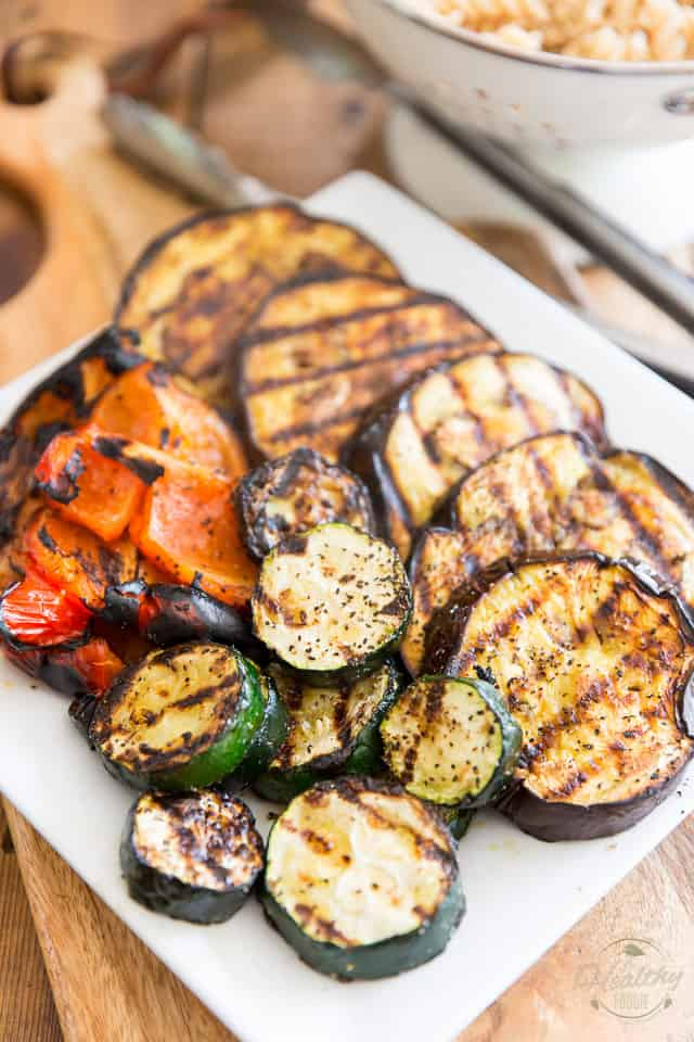 Grilled eggplant, zucchini and red bell peppers on a square white ceramic plate