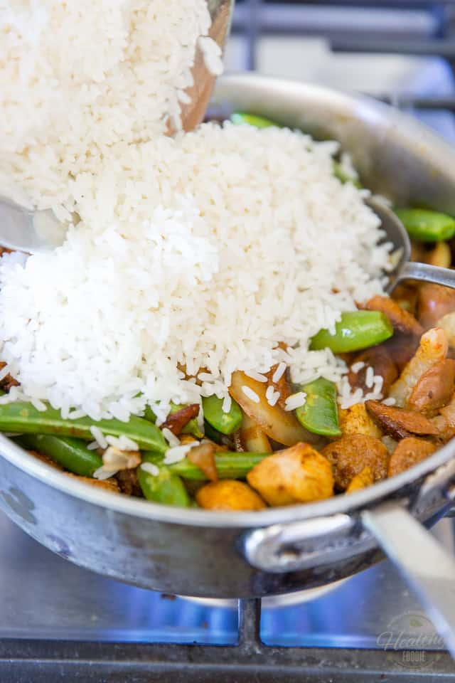 Rice is being added to a pan containing meat and veggies