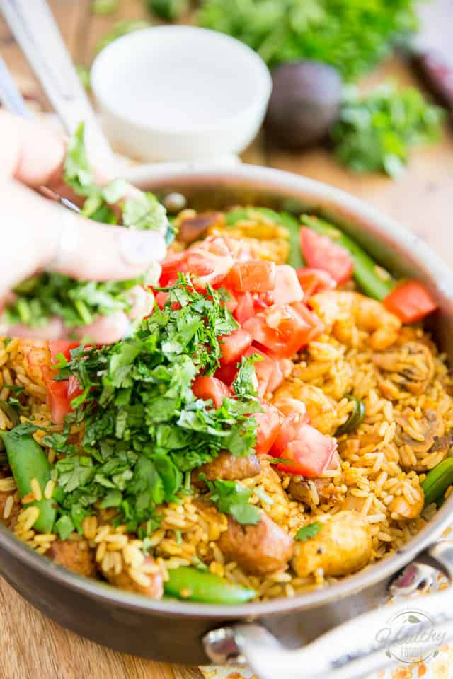 Tomatoes and cilantro are being added to Spanish Rice Casserole in a saute pan