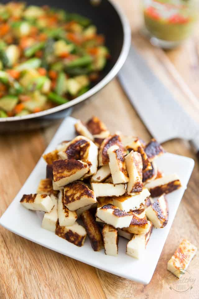 Grilled halloumi cheese cut into bite size pieces all piled up in a square white plate