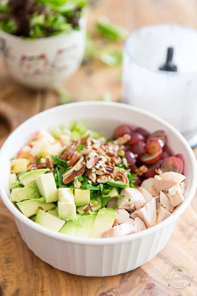 Cooked chicken, grapes, avocado, apples, pecans and parsley in a white ceramic bowl