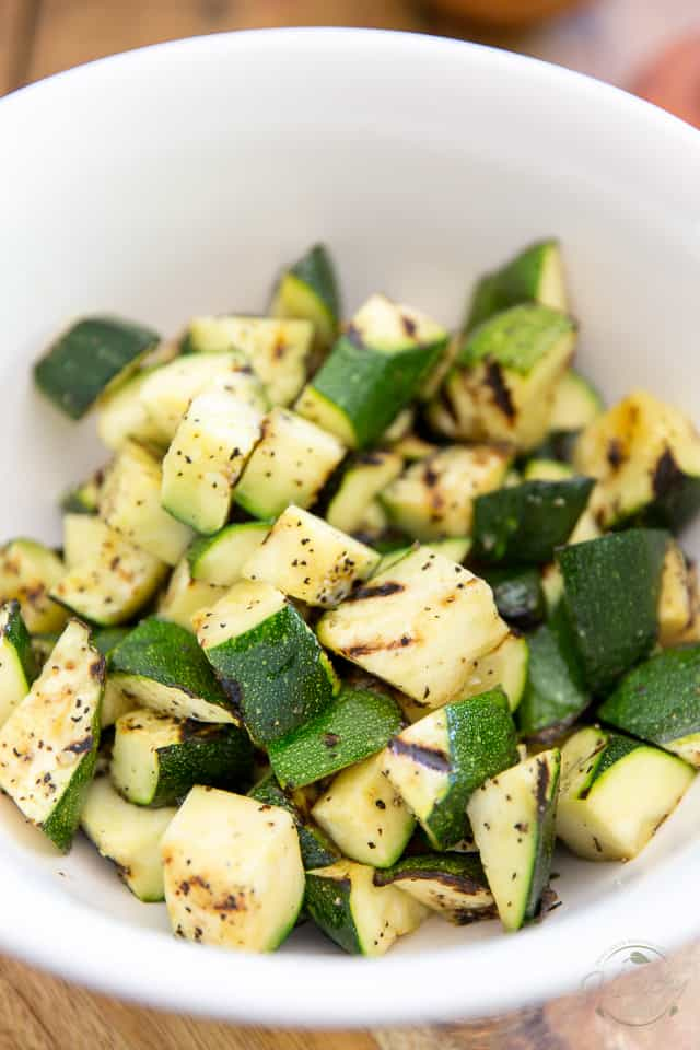 Grilled zucchini cut into bite size pieces in a white bowl