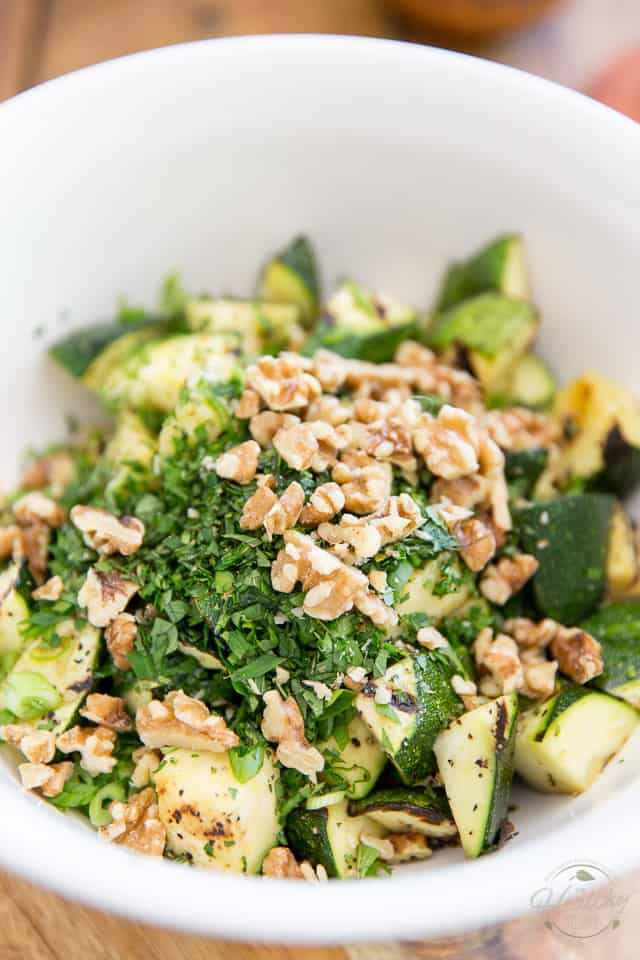 Grilled zucchini, walnuts and fresh herbs in a white bowl