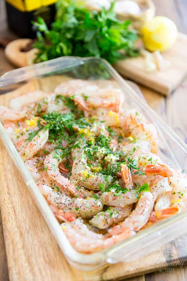 Raw shrimp with lemon zest parsley and garlic in a clear glass rectangular container