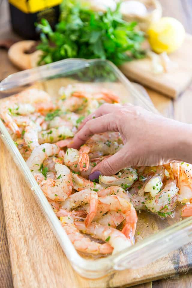 Raw shrimp with lemon zest parsley and garlic in a clear glass rectangular container, getting tossed around with hand