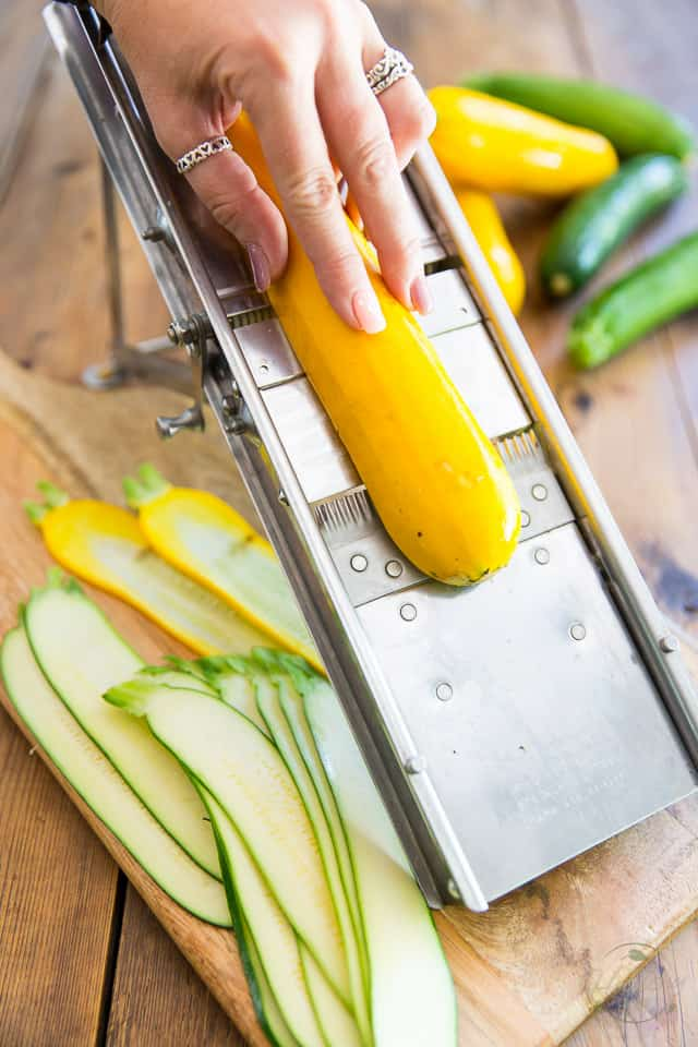 A yellow zucchini is being sliced with a mandolin