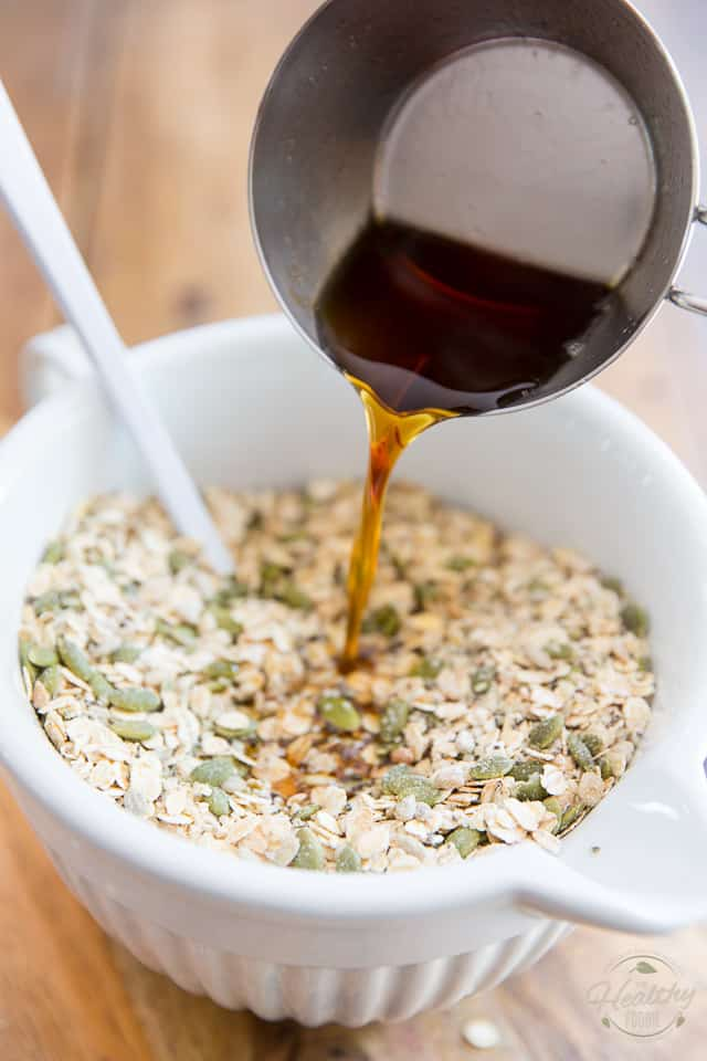 A mixture of hot syrup is getting poured into a bowl of raw cereal and seeds