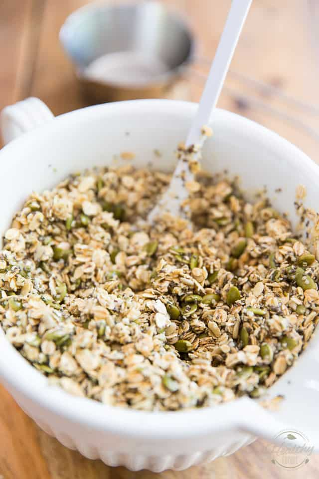 Raw granola mixture in a white ceramic bowl
