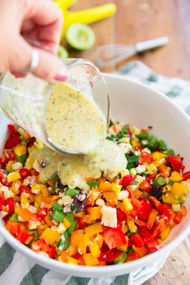 A creamy vinaigrette is being poured into a white bowl containing a colorful salad