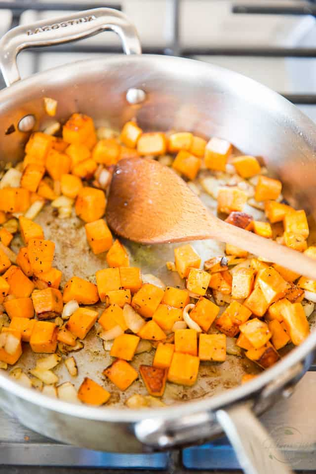 Sweet Potatoes and Onions are cooking in a stainless steel saute pan