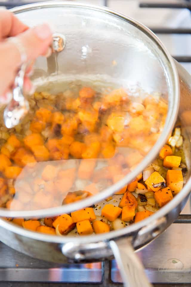 A lid is being placed over a saute pan containing sweet potatoes and onions