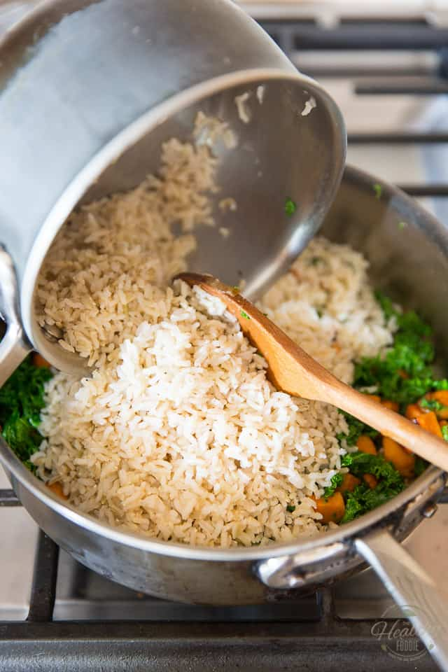 Cooked rice is getting poured into a saute pan