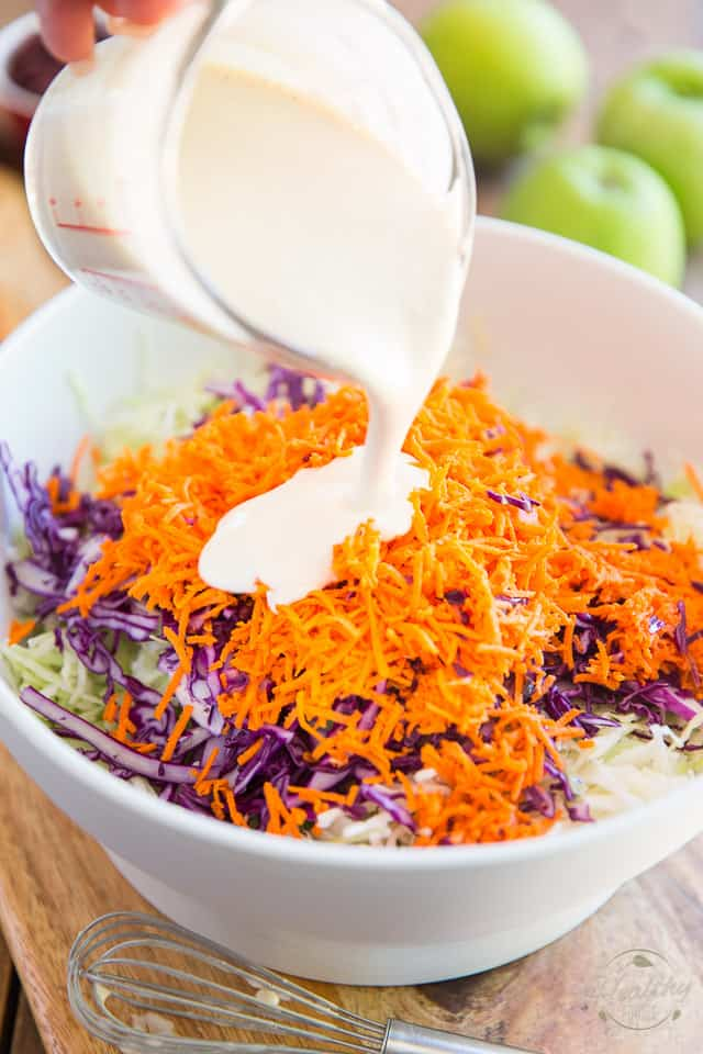 Shredded cabbage and carrots in a white bowl getting covered in creamy mayo dressing