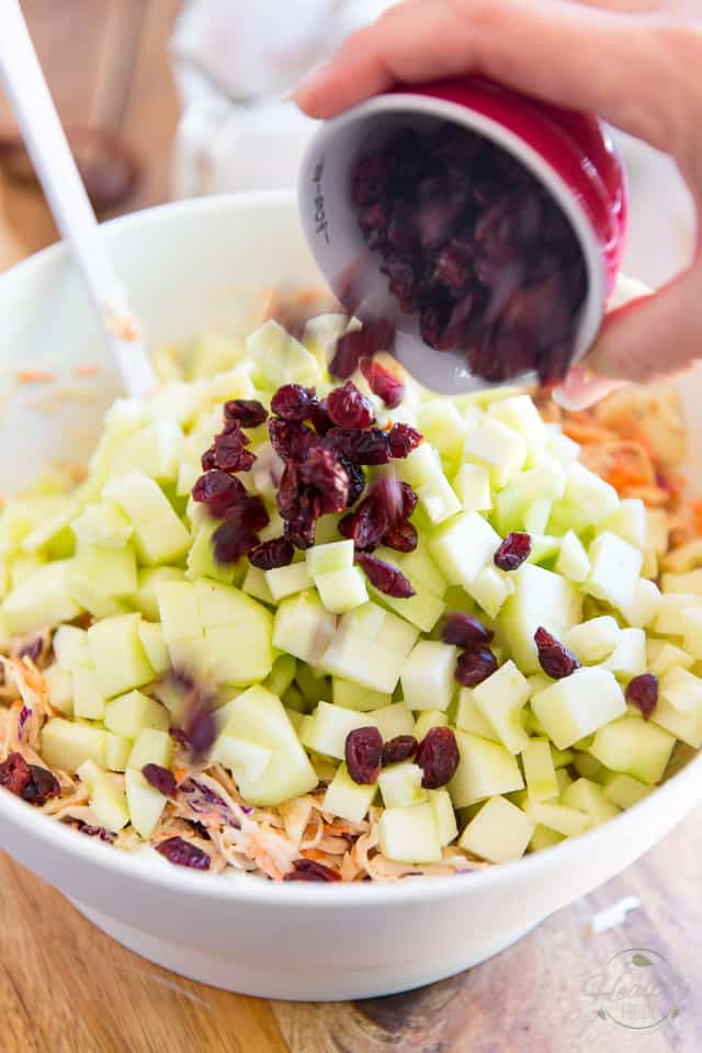 Apples and cranberries are being added to coleslaw in white ceramic bowl