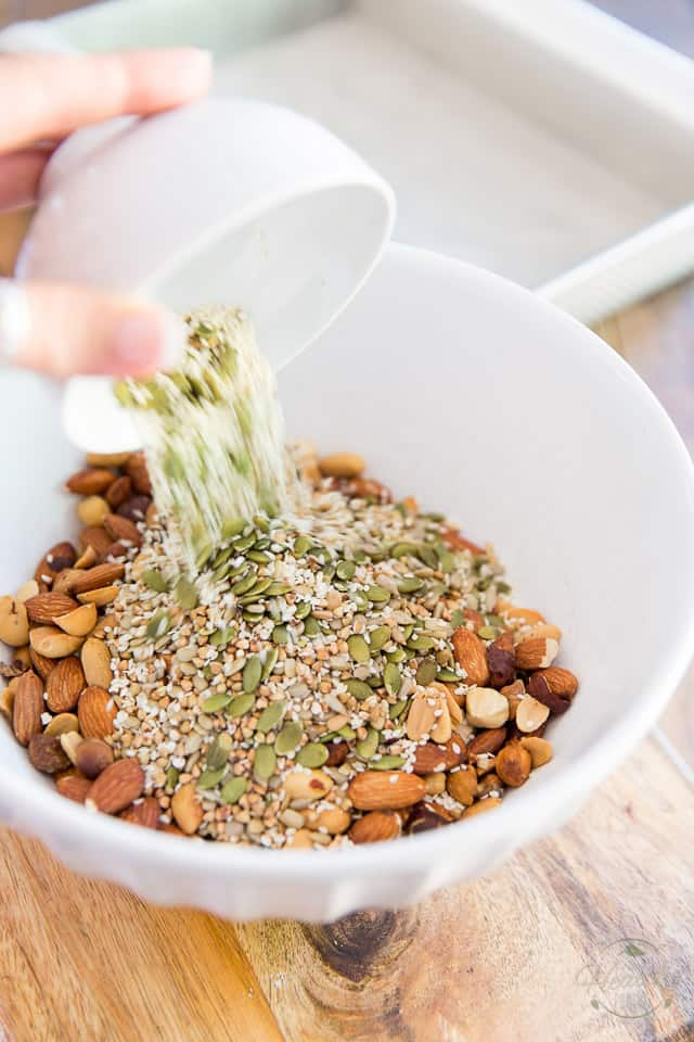 Seeds being added to a white bowl containing toasted nuts