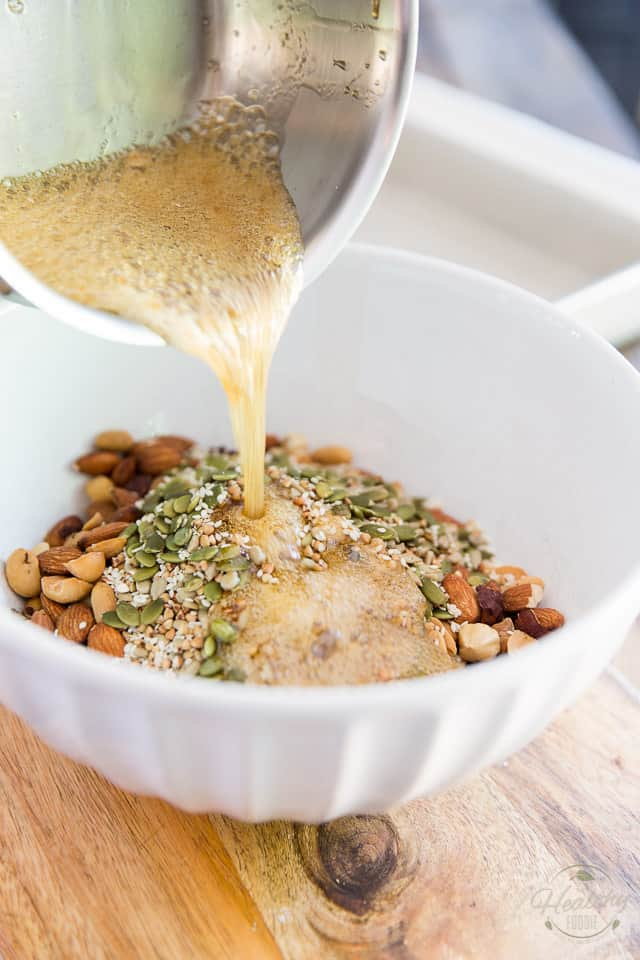 Hot syrup is poured onto white bowl containing a mixture of nuts and seeds