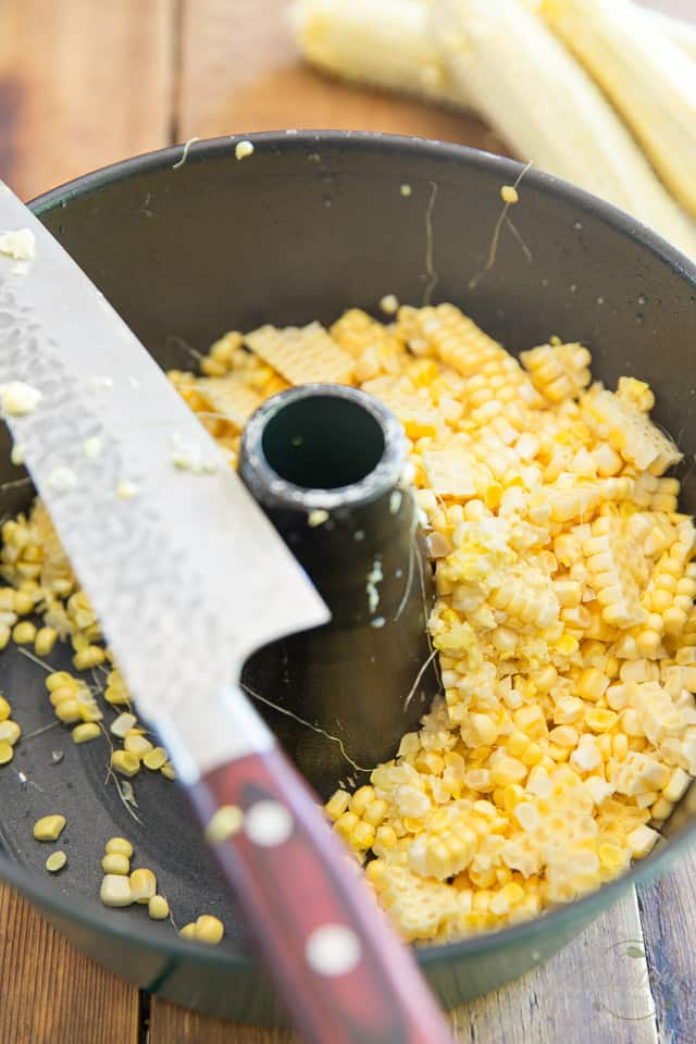Corn Kernels freshly removed from the cob sitting at the bottom of a Bundt pan with knife place across top of pan