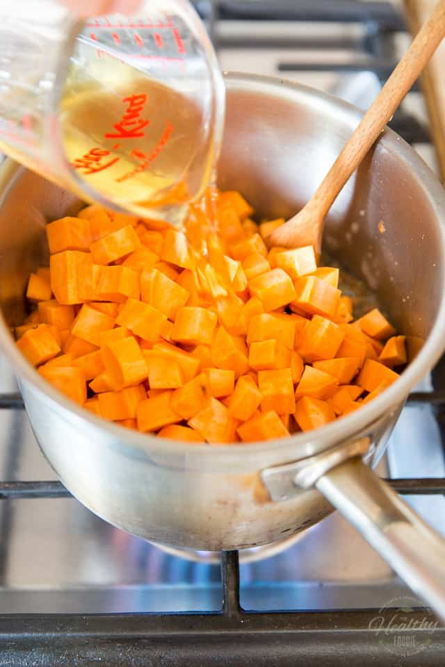 apple juice added to saucepan containing sweet potatoes