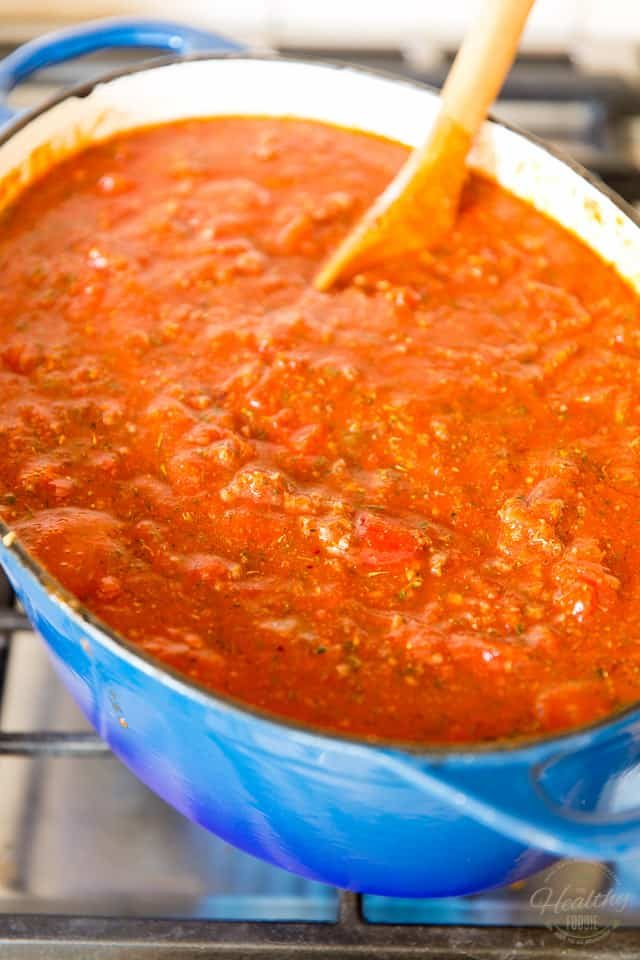 Spaghetti sauce cooking in a blue oval Dutch oven