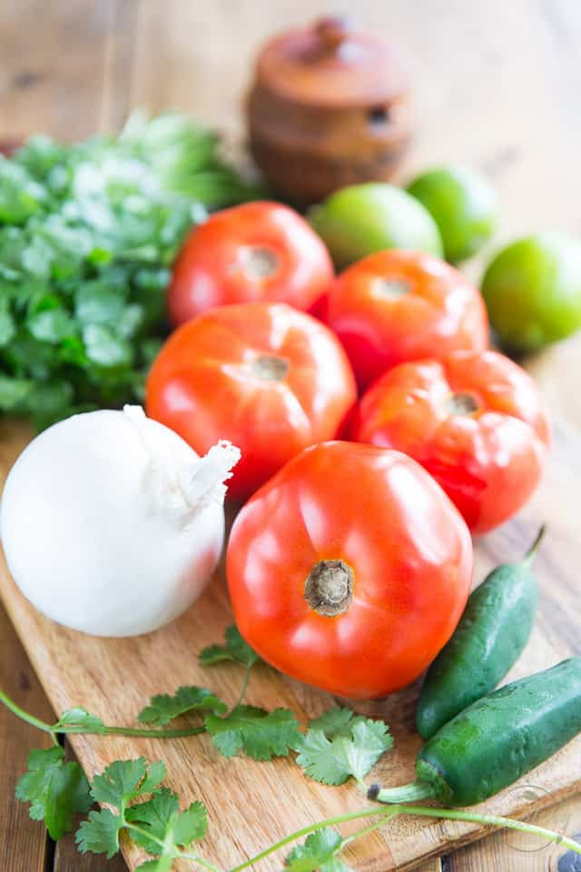 All the ingredients to make pico de gallo on a wooden cutting board