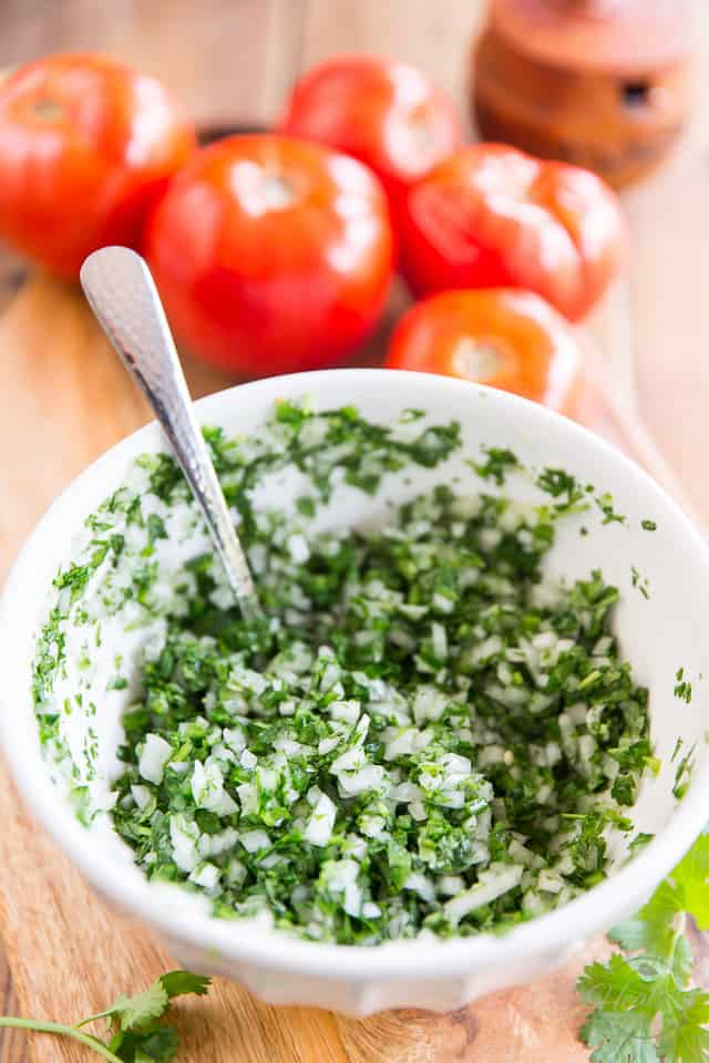 Chopped onions, jalapenos, cilantro, lime juice and salt marinating in a white bowl