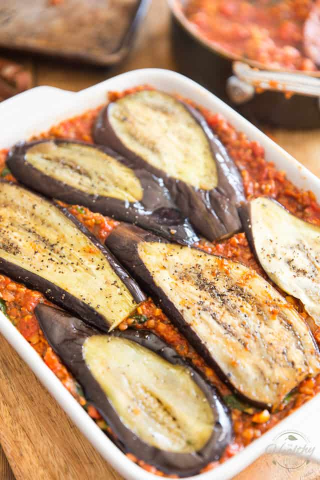 Vegetarian moussaka in the making - layering eggplant and sauce in a lasagna dish