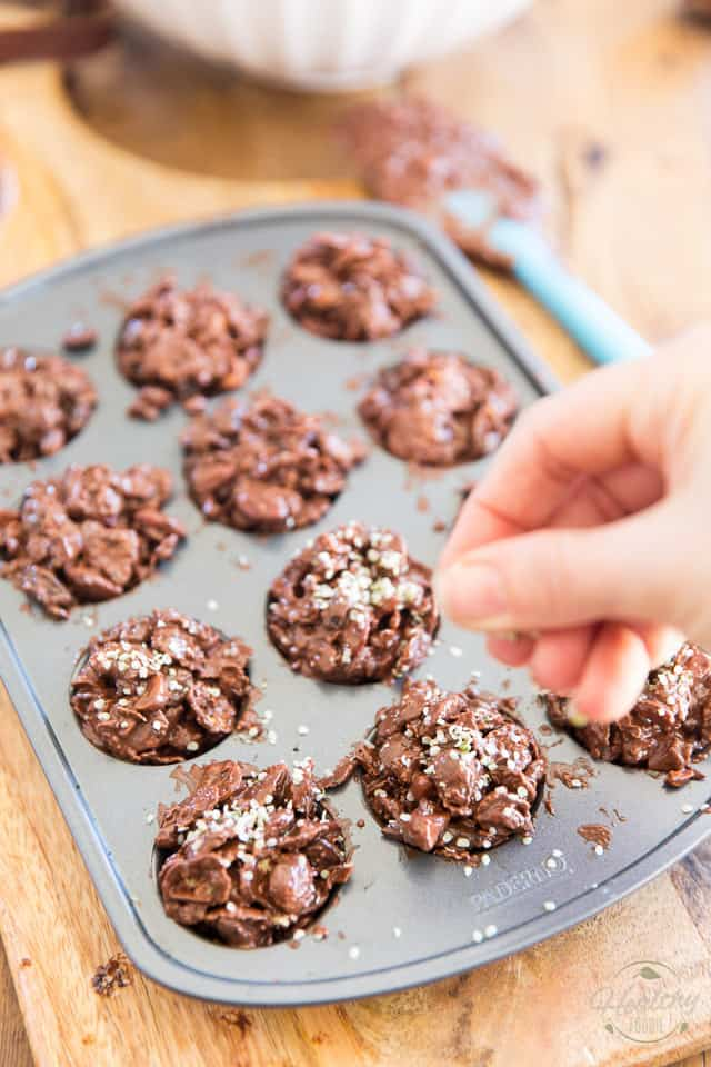 Sprinkling hemp hearts over unfinished chocolate clusters