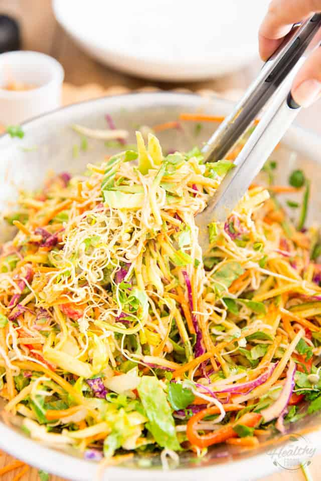 Tossing the salad with kitchen tongs until all the ingredients are well coated with the dressing