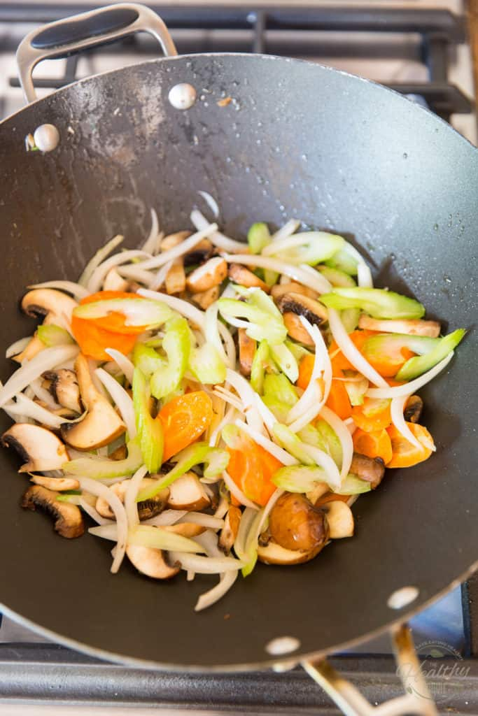 Saute the onion, celery, carrot and mushrooms in a large wok set over high heat
