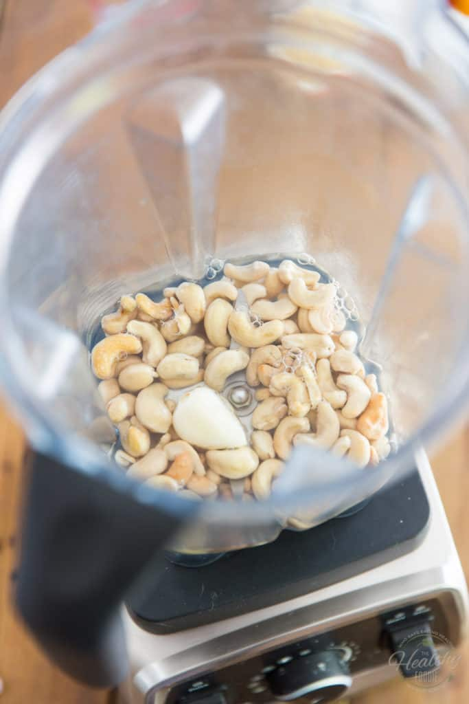 Place the raw cashews, boiling water and garlic in the container of your high-speed blender