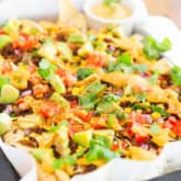 Spicy crumbled tempeh, loads of veggies and warm cashew queso scattered over a bed of organic corn tortilla chips... These Vegan Nachos with Spicy Crumbled Tempeh are the ultimate party food made good for you!