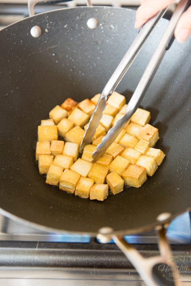 Cooking the tofu cubes in hot oil until crispy and golden brown