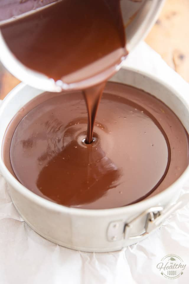 Pour the melted chocolate topping over the set cheesecake