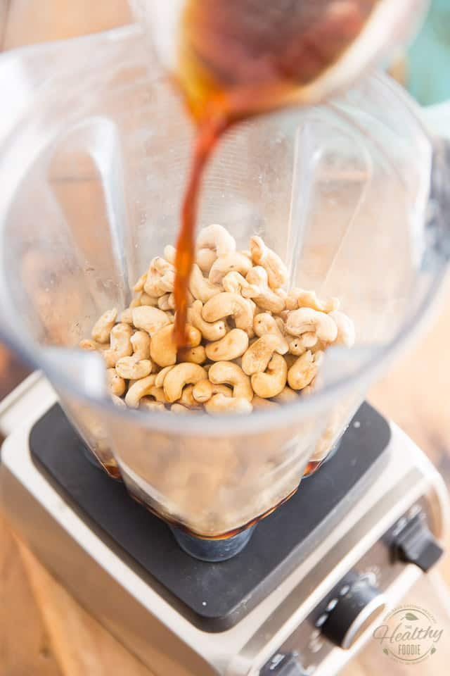 Combine cashews and hot coffee in the container of a high speed blender