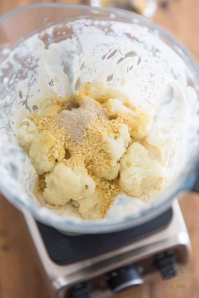 Add the cooked cauliflower and vegan parmesan to the high speed blender