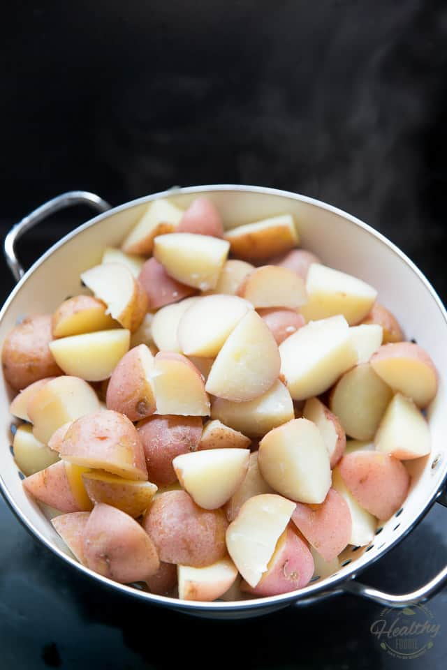 chunks of cooked potatoes cooling in a colander