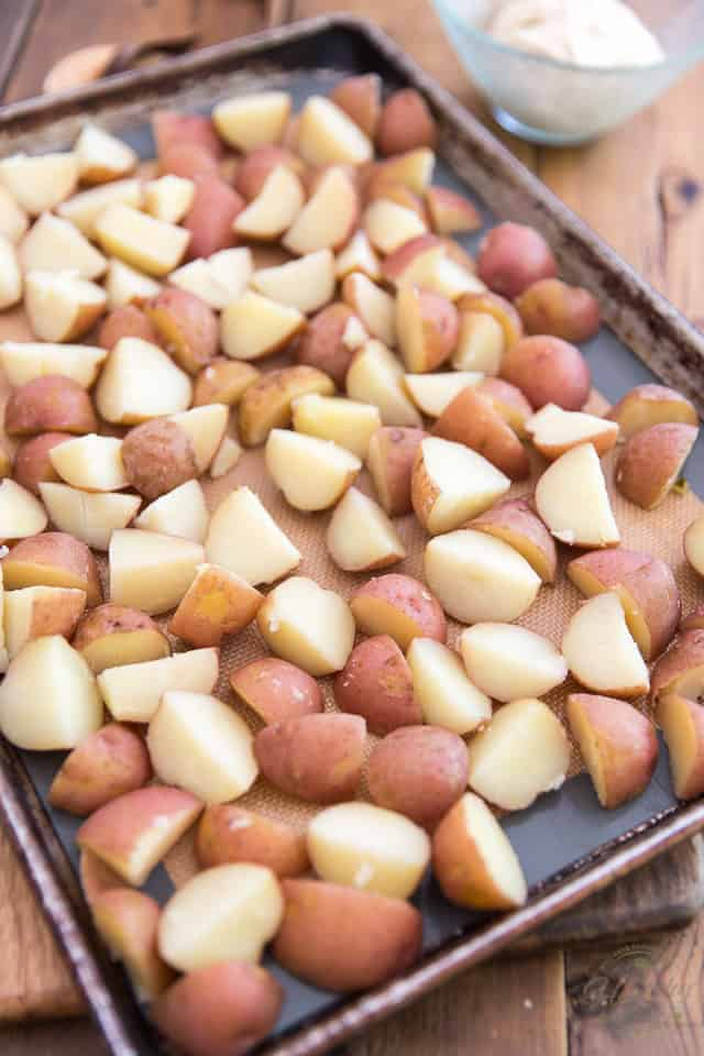 chunks of cooked potatoes arranged in a single layer on a baking sheet